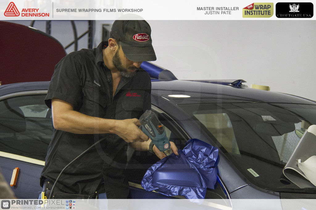 Justin Pate from The Wrap Institute heating Avery's Blue Metallic Supreme Wrap film onto a mirror with compound curves.